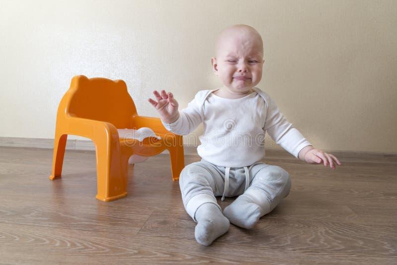 Pouco bebê que senta-se perto do potenciômetro e do grito imagens de stock royalty free