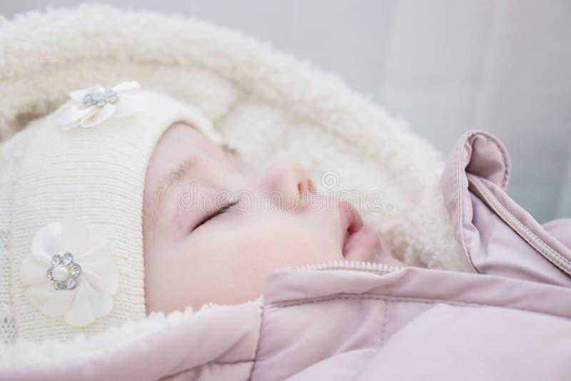Pouco bebê recém-nascido dorme no close-up do perfil da criança da roupa do inverno imagem de stock royalty free