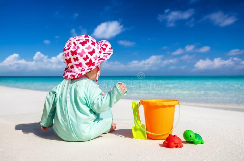 Pouco bebê senta-se em uma praia tropical e em jogos foto de stock royalty free