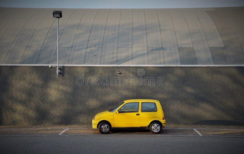 Pouco carro amarelo estacionou na frente de uma construção em Nijmegen os Países Baixos imagens de stock
