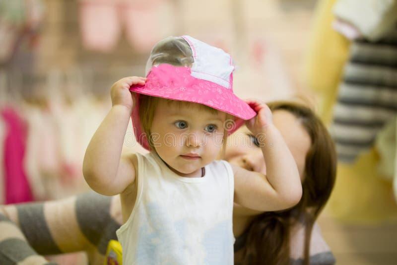 Pouco caucasiano tenta sobre o chapéu durante a compra com sua mamã fotos de stock