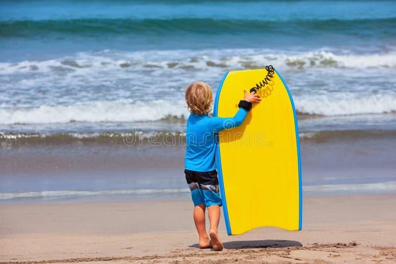 Pouco corrida do surfista com o bodyboard na praia do mar fotos de stock