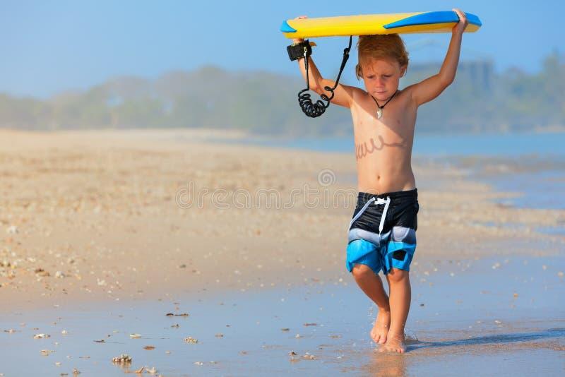 Pouco corrida do surfista com o bodyboard na praia do mar imagem de stock royalty free