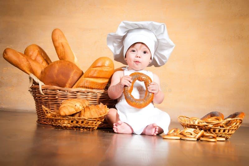 Pouco cozinheiro com um bagel em suas mãos fotos de stock