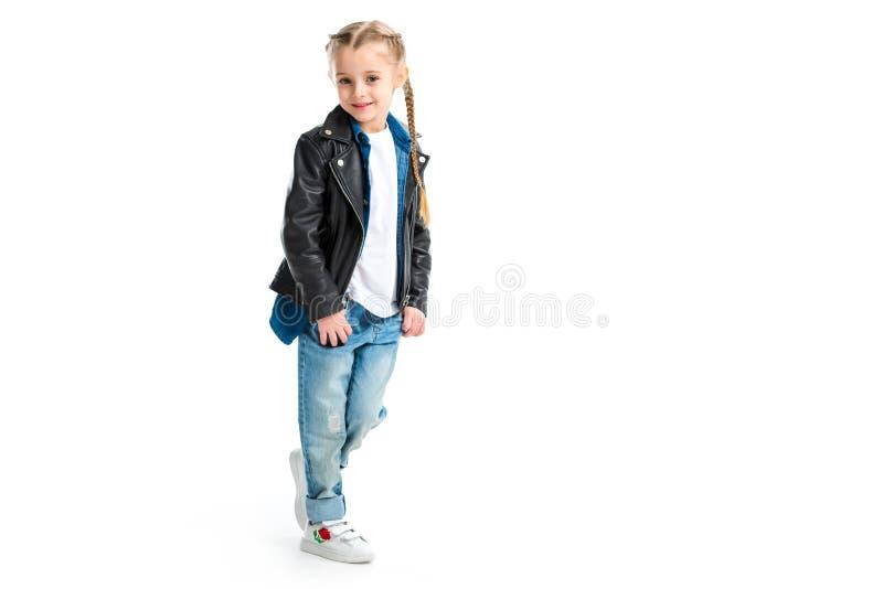 Pouco criança à moda que veste a posição preta do casaco de cabedal com os dedos em uns bolsos imagem de stock royalty free