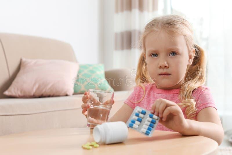 Pouco criança com comprimidos e água na tabela, espaço para o texto Perigo da intoxica??o do medicamento imagem de stock