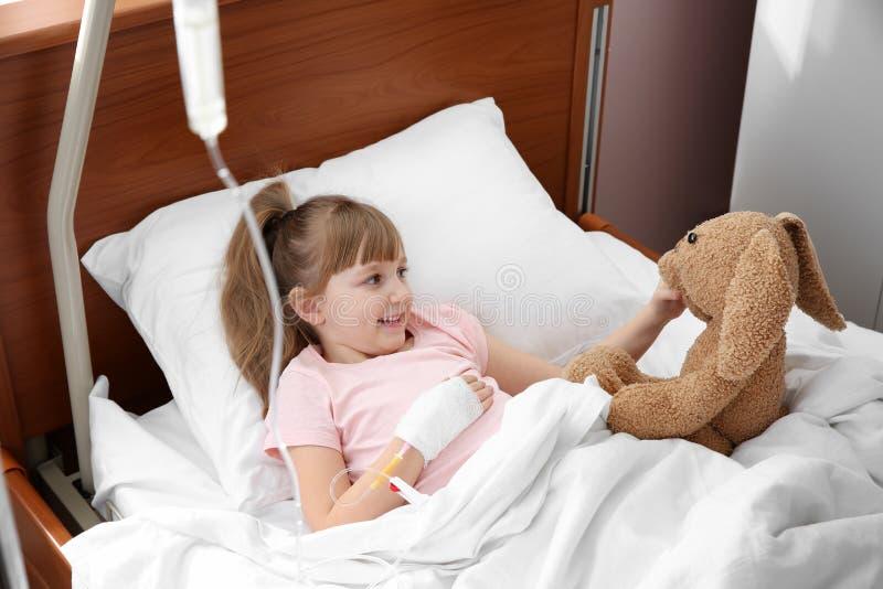 Pouco criança com gotejamento e o brinquedo intravenosos imagens de stock royalty free