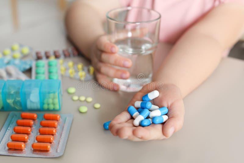 Pouco criança com muitos comprimidos diferentes e água no perigo da tabela da intoxicação do medicamento fotografia de stock
