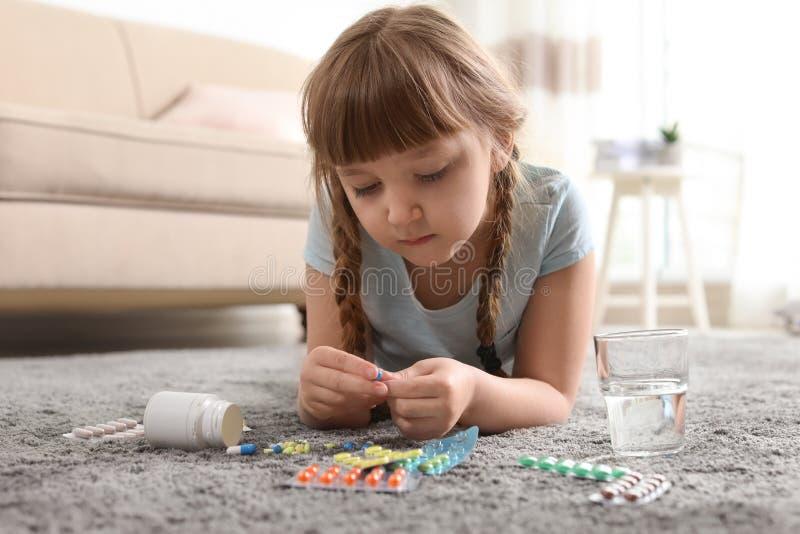Pouco criança com muitos comprimidos diferentes no assoalho Perigo da intoxica??o do medicamento fotografia de stock