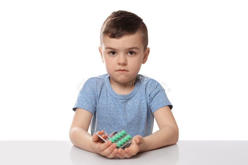 Pouco criança com os comprimidos diferentes no branco Perigo do agregado familiar imagem de stock royalty free
