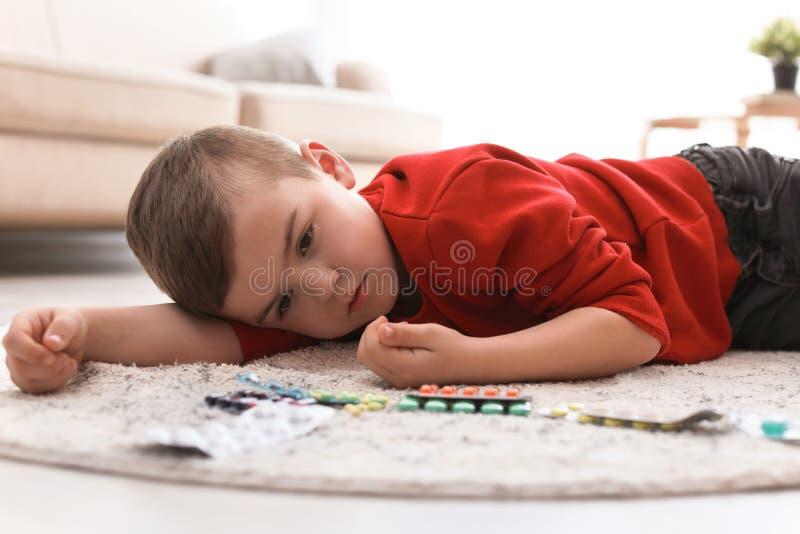 Pouco criança com os comprimidos que encontram-se no assoalho Perigo do agregado familiar imagens de stock