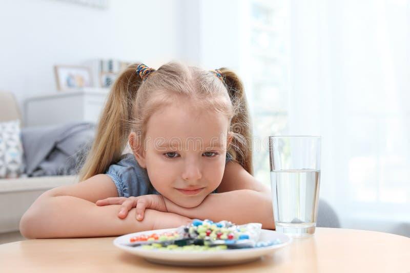 Pouco criança com a placa de comprimidos diferentes Perigo do agregado familiar foto de stock