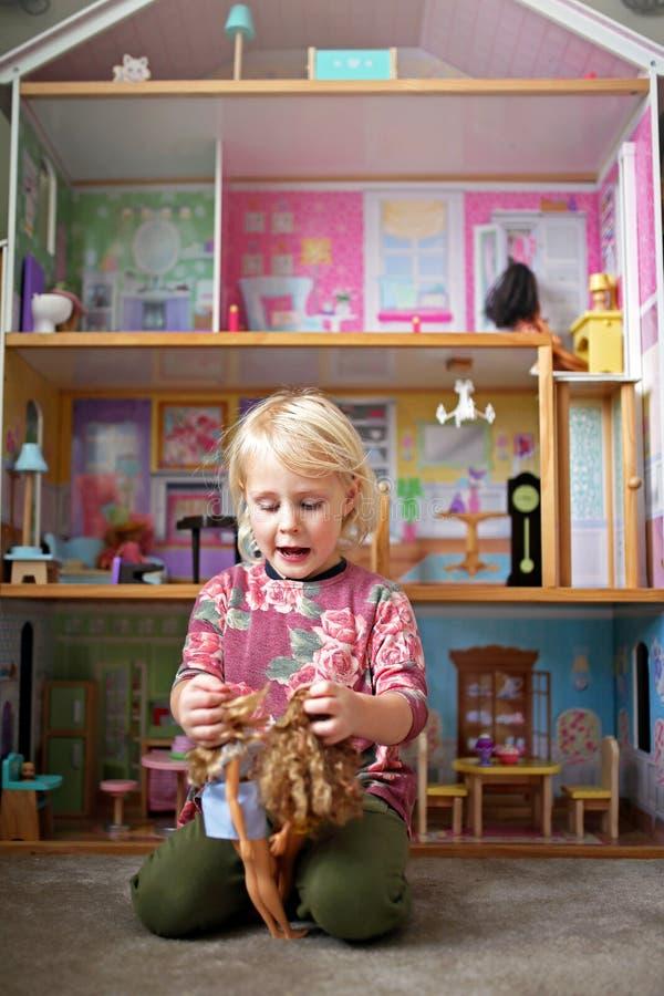 Pouco criança que joga brinquedos na frente de uma grande casa de boneca em seu quarto imagem de stock royalty free