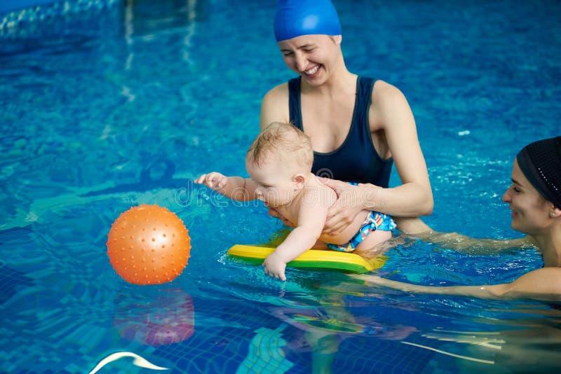 Pouco criança que joga na piscina Bebê que fica na água a bordo, tentando obtendo a bola de borracha alaranjada na água azul foto de stock royalty free
