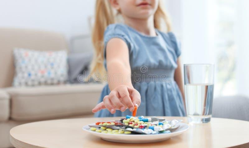 Pouco criança que toma o comprimido da placa Perigo do agregado familiar fotografia de stock