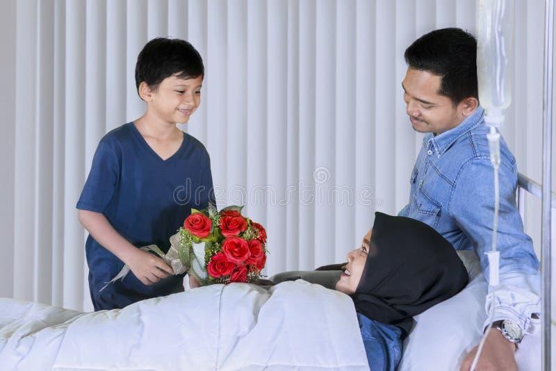 Pouco criança que visita sua mãe doente com seu pai imagens de stock