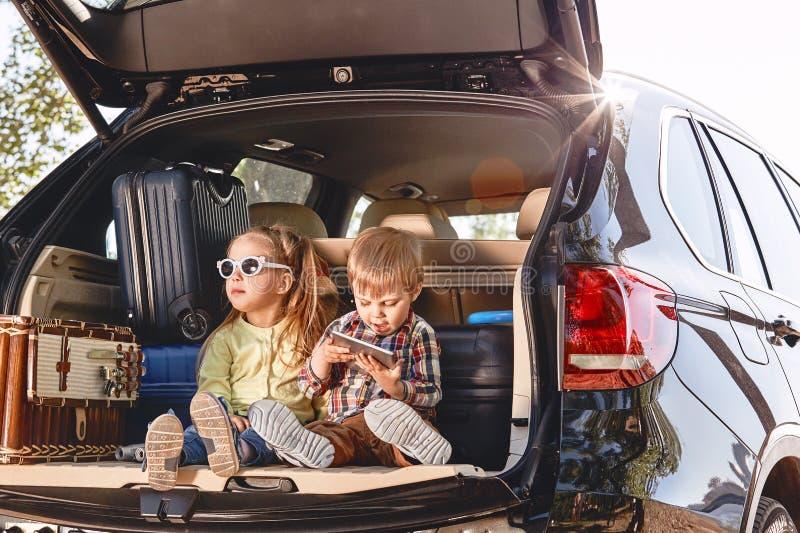 Pouco crianças bonitos que têm o divertimento no tronco de um carro preto com malas de viagem Viagem por estrada da família foto de stock