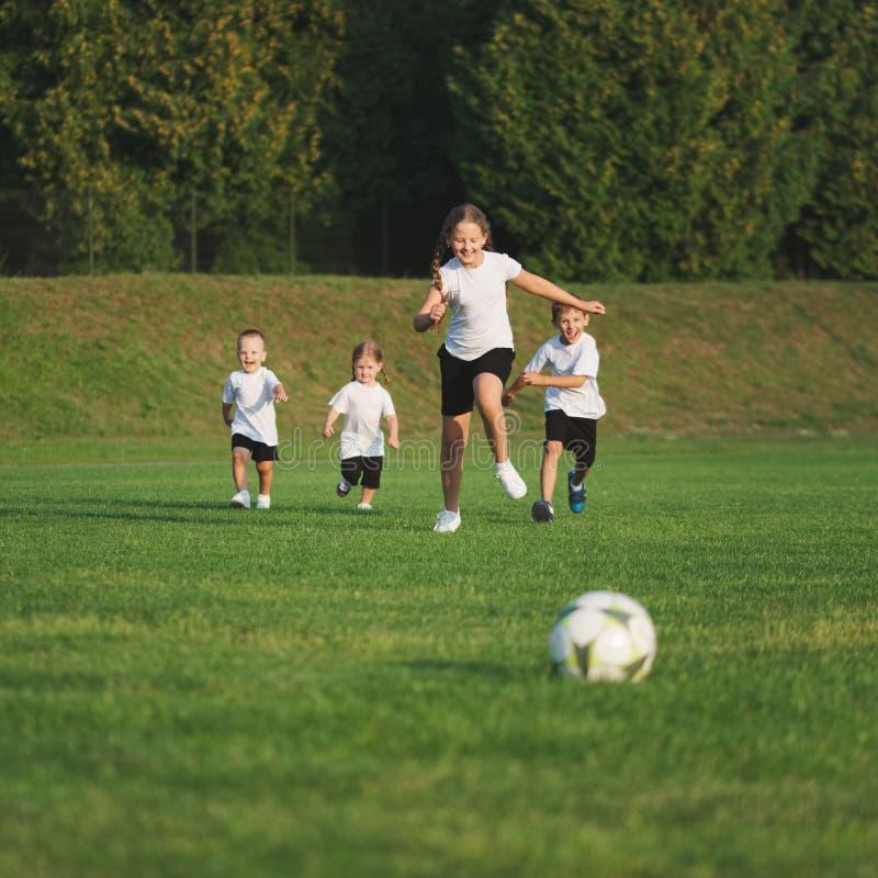 Pouco crianças felizes no campo de futebol imagem de stock