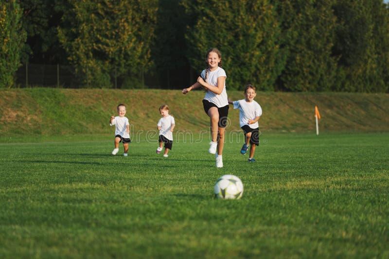 Pouco crianças felizes no campo de futebol fotografia de stock