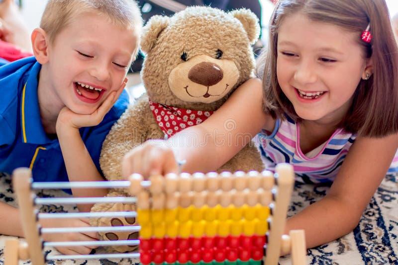 Pouco crianças que jogam com ábaco em casa Conceito da aprendizagem contar imagens de stock royalty free