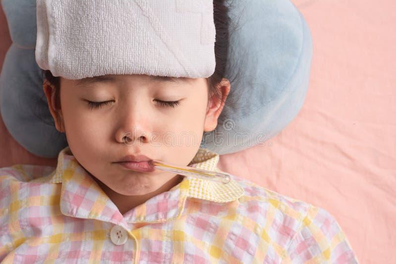 Pouco doente tailandês asiático da menina com toalha fria fotos de stock royalty free