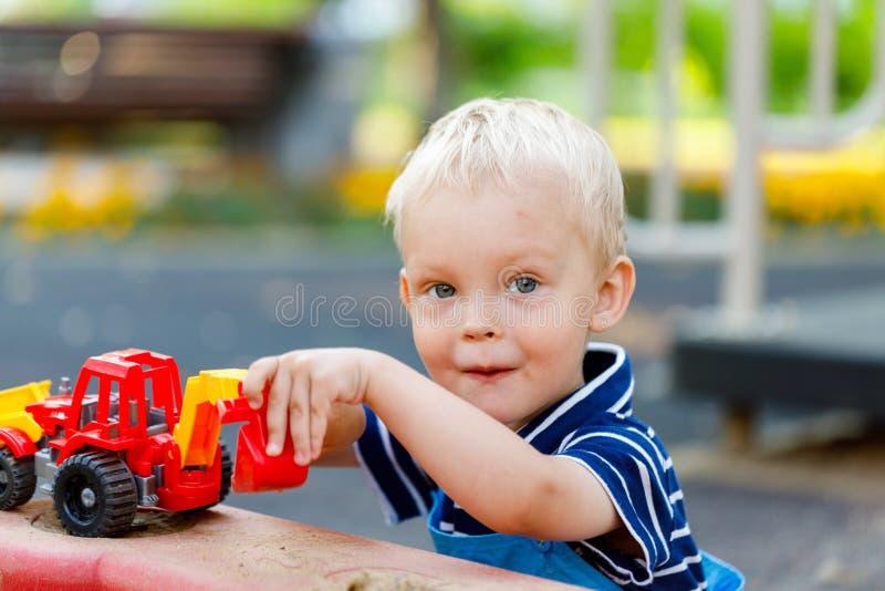 Pouco, dois anos de jogo de sorriso do menino idoso na caixa de areia usando uma máquina escavadora fotos de stock royalty free