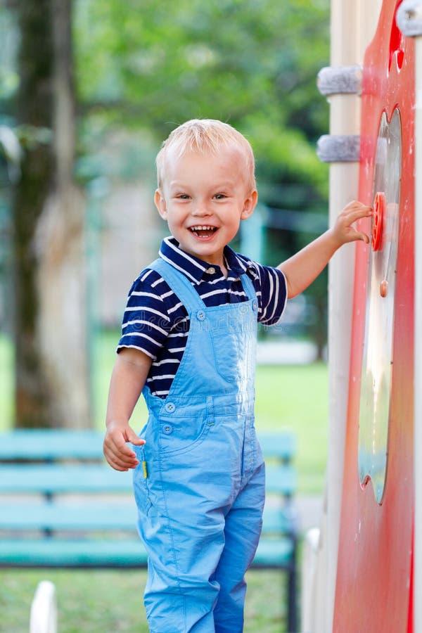 Pouco, dois anos de jogo de sorriso do menino idoso no campo de jogos fotografia de stock