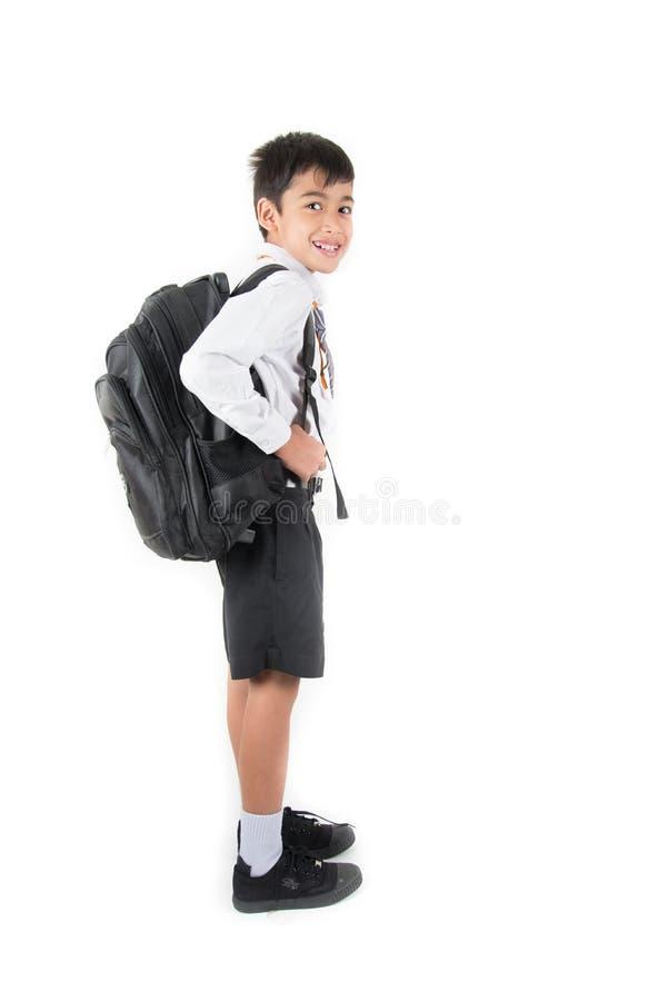 Pouco estudante vestindo do menino de escola uniforme apronta-se para o primeiro dia foto de stock