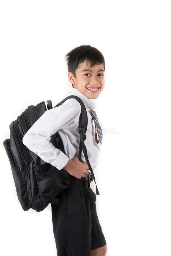 Pouco estudante vestindo do menino de escola uniforme apronta-se para o primeiro dia foto de stock royalty free