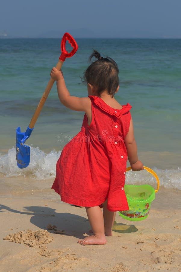 Pouco filha pronta para jogar com a areia na praia fotos de stock royalty free