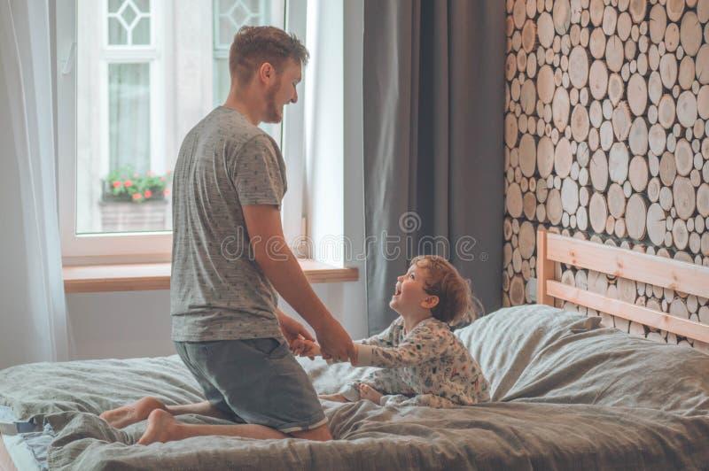 Pouco filho que joga com o pai no sofá Fam?lia loving feliz Criança que aprecia o jogo com paizinho em casa Conceito do dia de pa imagens de stock royalty free