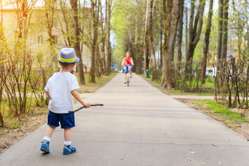 Pouco intimidação-menino bonito com uma vara que olha um ciclista no passeio imagem de stock royalty free