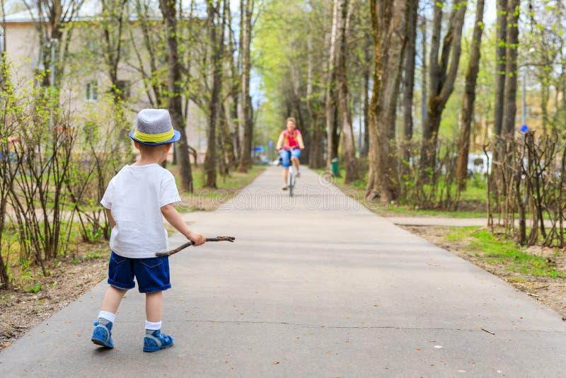 Pouco intimidação-menino bonito com uma vara que olha um ciclista no passeio foto de stock