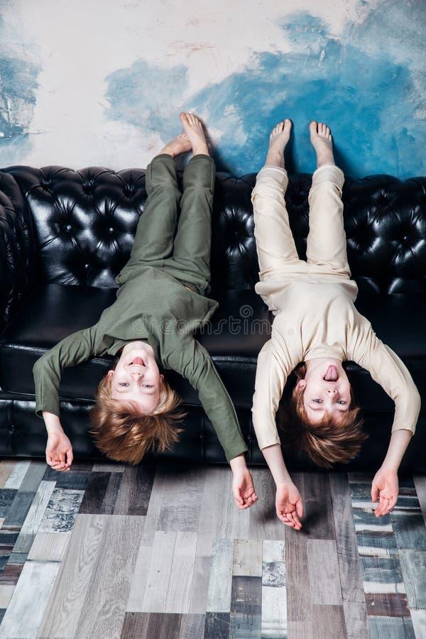 Pouco irmãos gêmeos nos pijamas que têm a sala do divertimento em casa fotos de stock royalty free