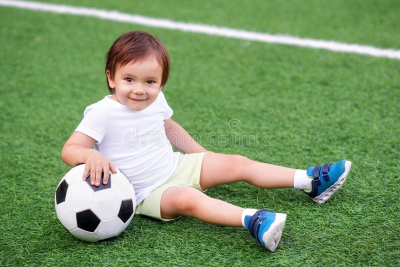 Pouco jogador de futebol que senta-se em um campo de futebol verde com uma bola e um sorriso Retrato de uma criança feliz que jog fotos de stock royalty free