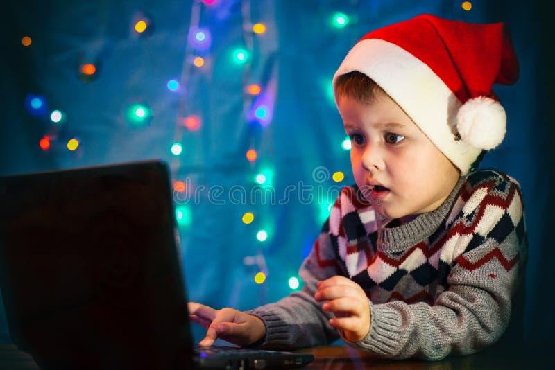 Pouco letra da escrita da criança a Santa Claus no laptop Rapaz pequeno com chapéu de Santa fotos de stock