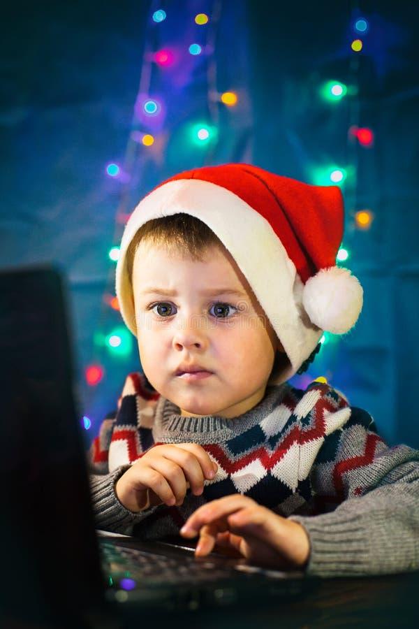 Pouco letra da escrita da criança a Santa Claus no laptop Rapaz pequeno com chapéu de Santa foto de stock