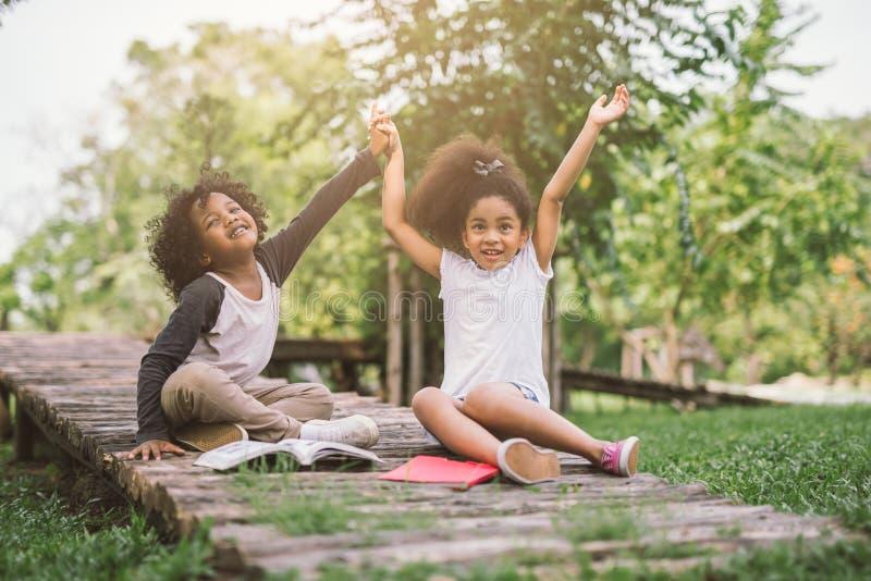 Pouco livro de leitura da menina da criança do Afro entre o verde crava o jardim do prado com amigo fotos de stock royalty free