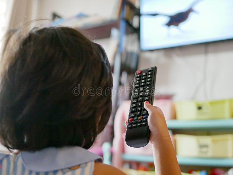 Pouco a mão do bebê asiático que guarda um controlo a distância da televisão, ao olhá-lo em casa fotografia de stock