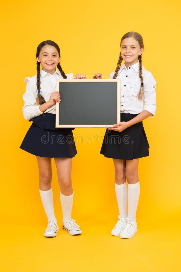 Pouco mas esperto Pouco alunos que guardam o quadro-negro no fundo amarelo Pouco crianças com o quadro-negro para fotos de stock royalty free