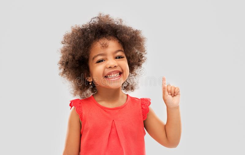 Pouco menina afro-americano que aponta o dedo acima fotografia de stock royalty free