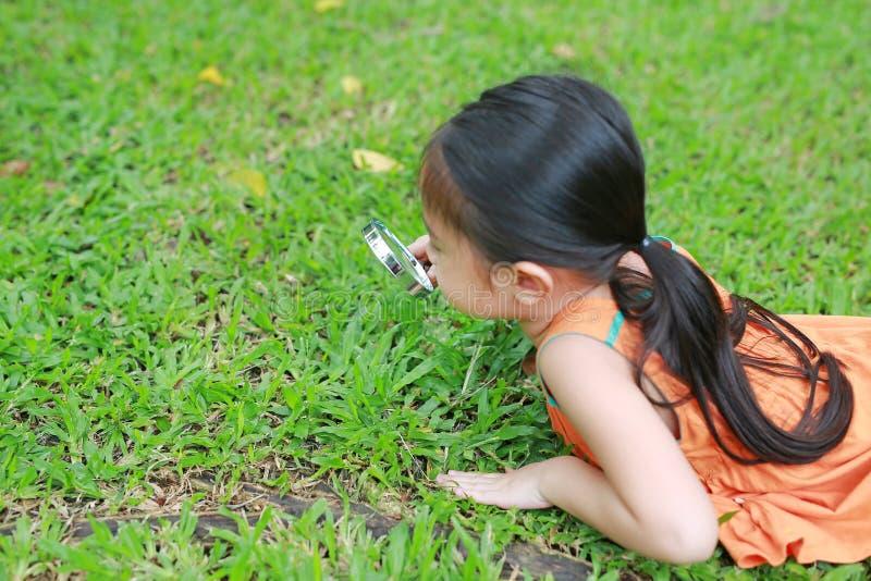 Pouco menina asiática da criança com a lupa no jardim da grama verde Natureza do close-up como o pesquisador fotos de stock royalty free