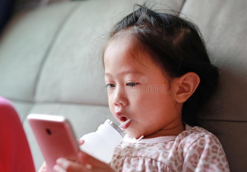 Pouco menina asiática que joga o telefone esperto e o leite bebendo com palha no sofá em casa fotos de stock