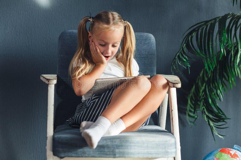 Pouco menina blondy que senta-se em uma cadeira e que faz os trabalhos de casa para a escola, pesquisando a informação na tabulet foto de stock