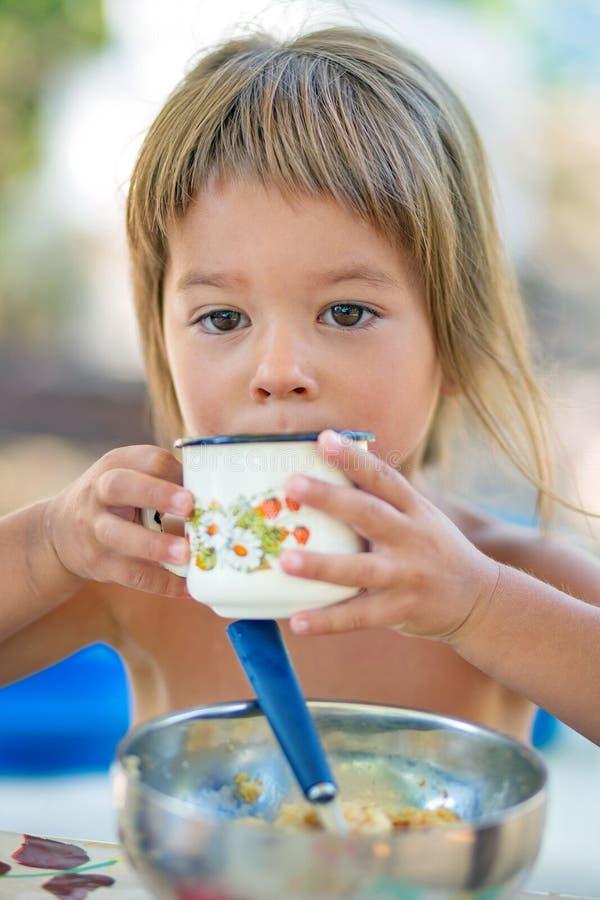 Pouco menina bonita está bebendo o chá fotos de stock
