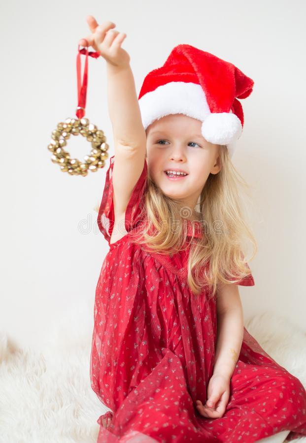 Pouco menina bonita no Natal de espera de Santa Hat Red Party Dress e no ano novo fotografia de stock