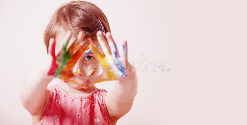 Pouco menina bonito com a composi??o colorida das crian?as que mostra as m?os pintadas Conceito feliz da infância e da arte Foco  fotos de stock