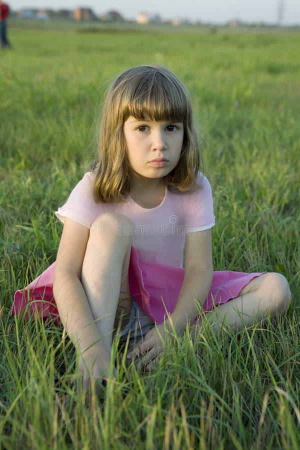 Pouco menina bonito da virada que senta-se na grama imagem de stock