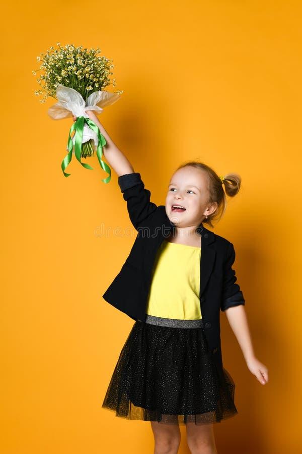 Pouco menina bonito dos anos de idade 5 guarda um grande ramalhete das margaridas fotografia de stock royalty free
