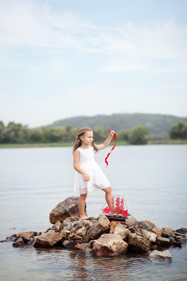 Pouco menina bonito e escarlate das velas Menina que senta-se nas rochas no oceano do litoral com o navio ?rvore no campo Infânci fotos de stock